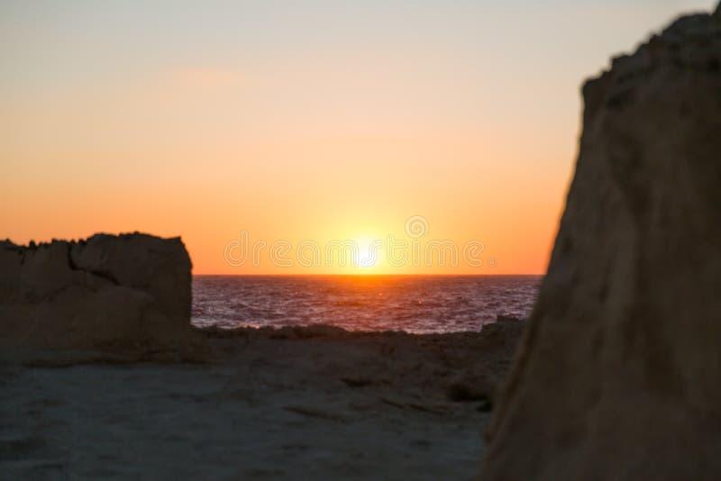 Por do sol sobre os penhascos da pedra calcária da ilha de Gozo e o mar Mediterrâneo W foto de stock