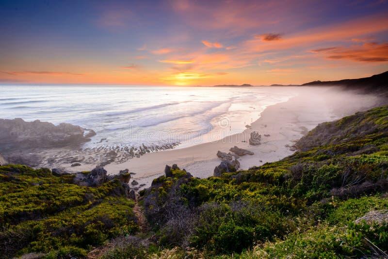Por do sol sobre a praia do brenton-em-mar em África do Sul fotografia de stock