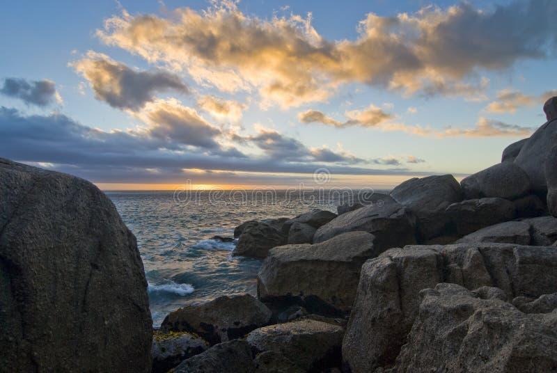 Por do sol sobre a praia rochosa imagem de stock