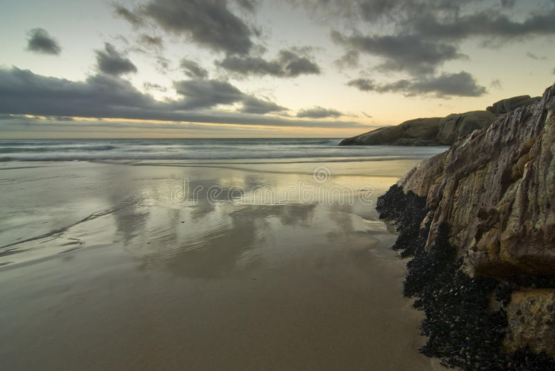 Por do sol sobre a praia rochosa fotografia de stock royalty free