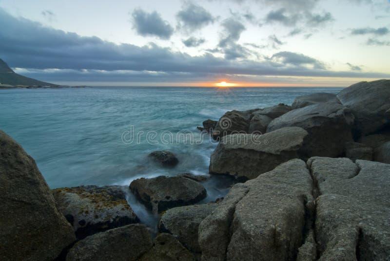 Por do sol sobre a praia rochosa foto de stock