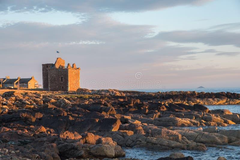 Por do sol sobre ruínas velhas de Portencross Escócia imagens de stock