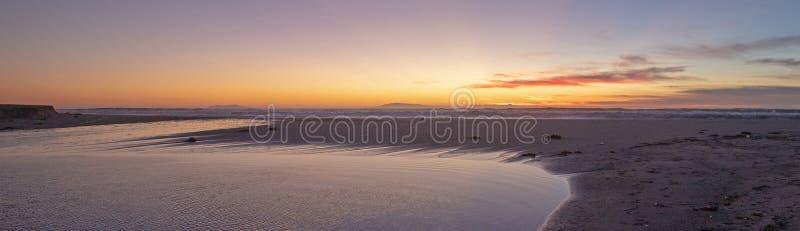 Por do sol sobre a saída maré de Santa Clara River ao Oceano Pacífico no parque estadual de McGrath na costa de Califórnia em Ven foto de stock