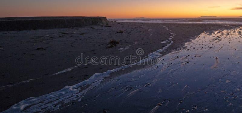 Por do sol sobre a saída maré de Santa Clara River ao Oceano Pacífico no parque estadual de McGrath na costa de Califórnia em Ven imagem de stock royalty free