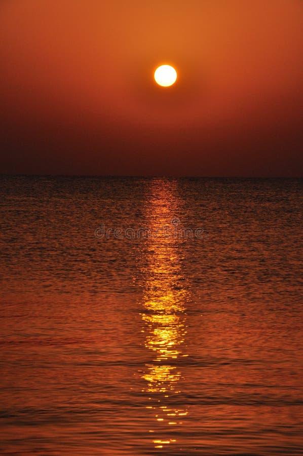 Por do sol sobre a superfície do mar com reflexões dos raios na superfície foto de stock