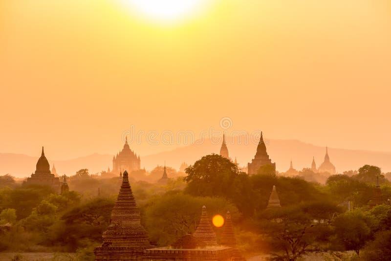 Por do sol sobre templos do pagode com névoa de Bagan em Myanmar foto de stock