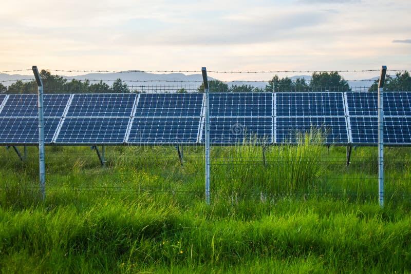Por do sol sobre um central elétrica fotovoltaico com os módulos fotovoltaicos para a energia renovável no campo Gera??o das ener fotografia de stock