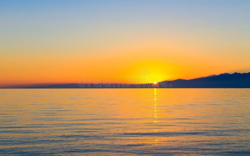 Por do sol sobre um lago cercado por montanhas imagem de stock royalty free