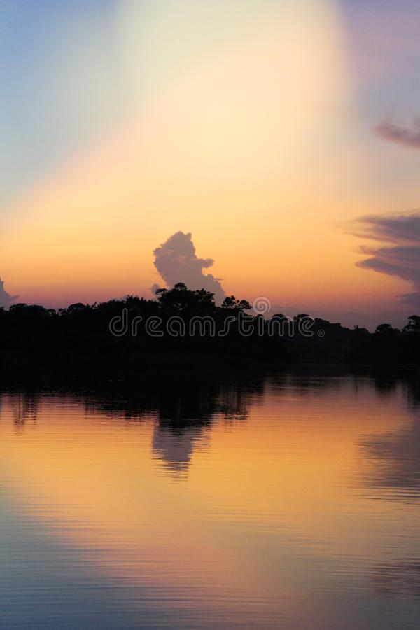 Por do sol sobre um rio com reflexões das árvores contra a luz foto de stock