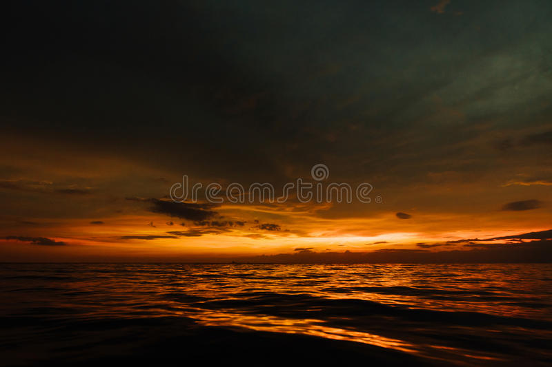 Por do sol sombrio no mar da noite Por do sol bonito no céu nebuloso no oceano fotografia de stock royalty free