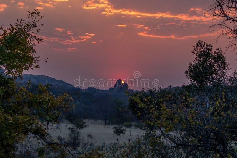 Por do sol surpreendente atrás das rochas de equilíbrio, montes de Matobo, Zimbabwe imagens de stock royalty free