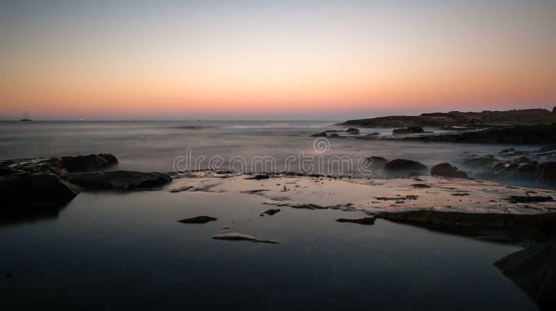 Por do sol surpreendente do fulgor alaranjado com oceano calmo imagens de stock