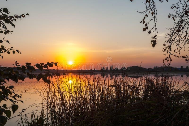 Por do sol surpreendente sobre o lago Reflexão colorida na água foto de stock royalty free