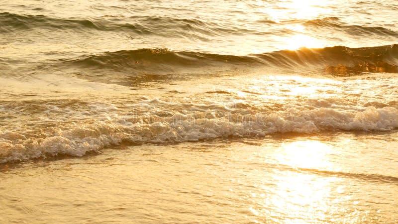 Por do sol surpreendente sobre a praia tropical a praia do oceano acena na praia no tempo do por do sol, luz solar reflete na sup imagem de stock royalty free