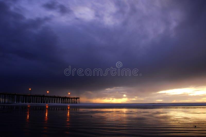 Por do sol tormentoso com cais e luzes fotos de stock