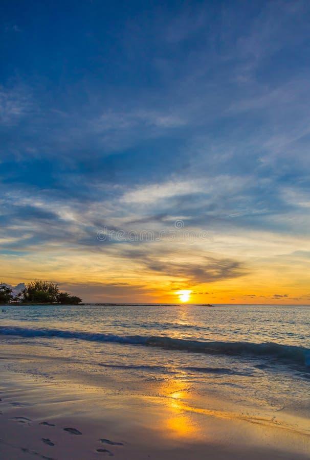 Por do sol tropical com o sol que reflete fora da água e da areia molhada fotos de stock royalty free