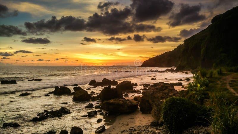 Por do sol tropical na praia Praia de Menganti, Kebumen, Java central, Indonésia fotografia de stock