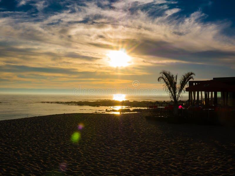 Por do sol vívido bonito sobre o Oceano Atlântico de Povoa de Varzim, Porto, Portugal com a barra mostrada em silhueta da palmeir fotografia de stock royalty free