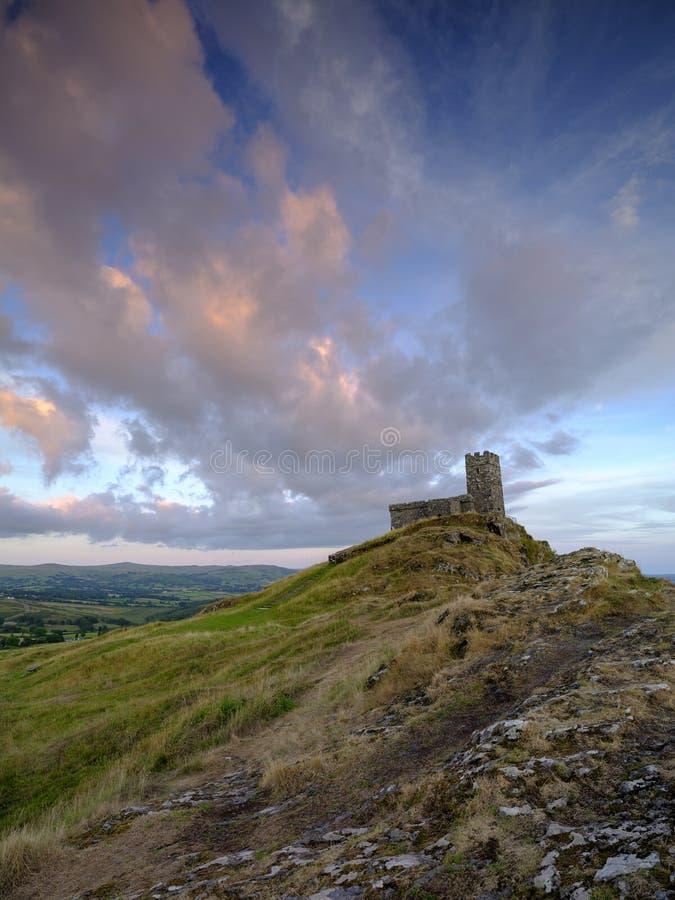 Por do sol do ver?o sobre Brentor, com a igreja de St Michael de Rupe - St Michael da rocha, na borda do nacional de Dartmoor imagens de stock royalty free