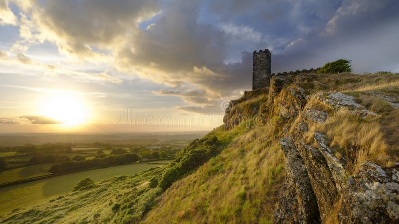 Por do sol do ver?o sobre Brentor, com a igreja de St Michael de Rupe - St Michael da rocha, na borda do nacional de Dartmoor fotos de stock