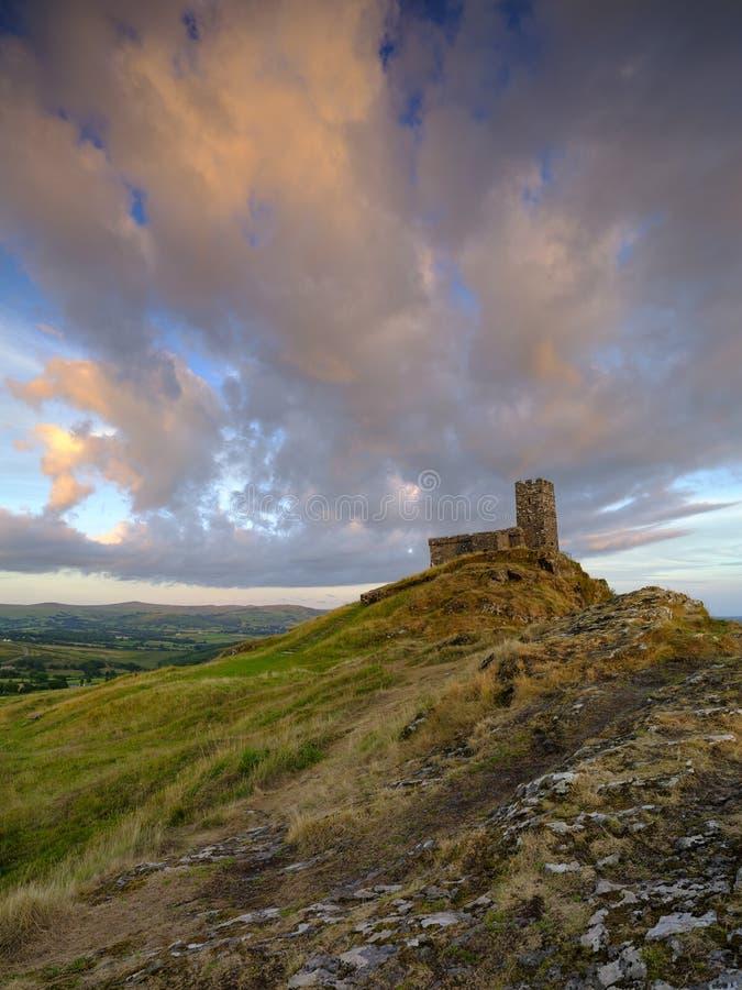 Por do sol do ver?o sobre Brentor, com a igreja de St Michael de Rupe - St Michael da rocha, na borda do nacional de Dartmoor imagens de stock