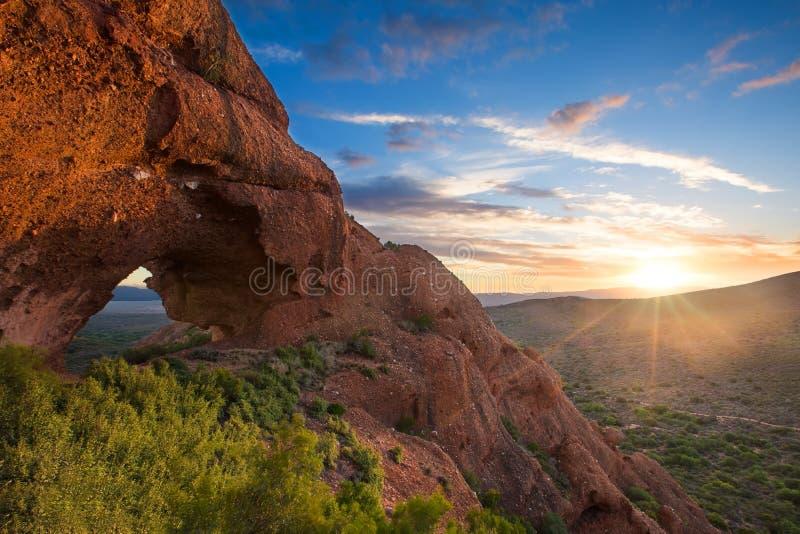 Por do sol vermelho do arco da montanha da rocha com as nuvens perto de Calitzdorp em Sou foto de stock royalty free