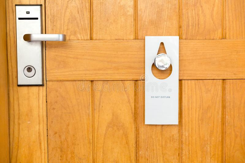 Por favor n?o perturbe o sinal na porta de madeira Closed da sala de hotel fotografia de stock royalty free