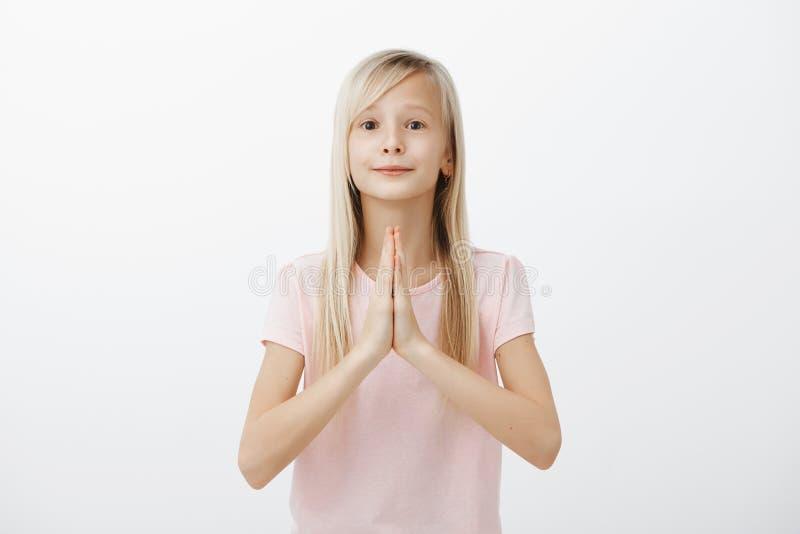 Por favor papá, seré buena muchacha si usted me compra presente Retrato de hacer muecas a la mujer joven feliz en camiseta rosada imagen de archivo libre de regalías