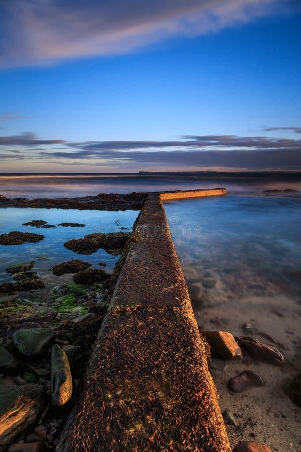 Por la costa de montañas escocesas - tiempo de la puesta del sol en la playa fotos de archivo