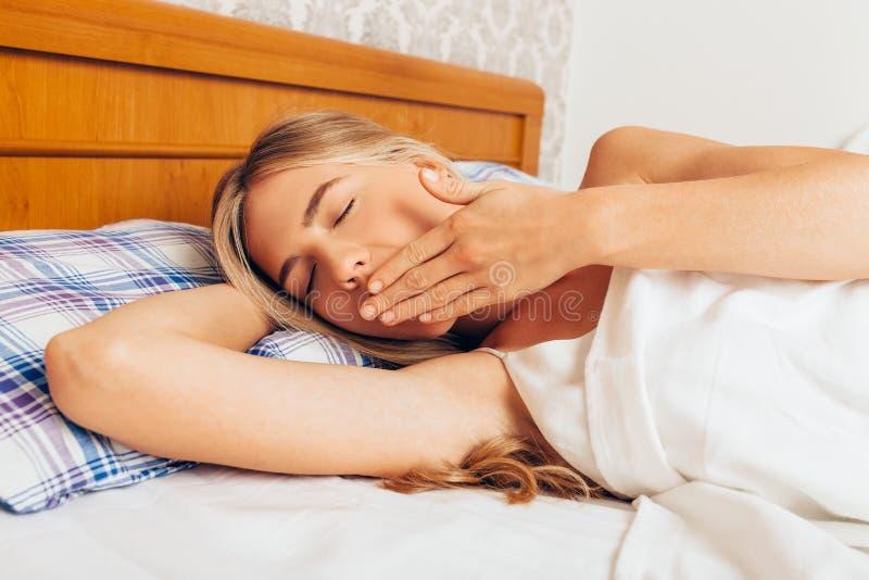 Por la mañana una muchacha atractiva en el dormitorio que despertó y imagen de archivo