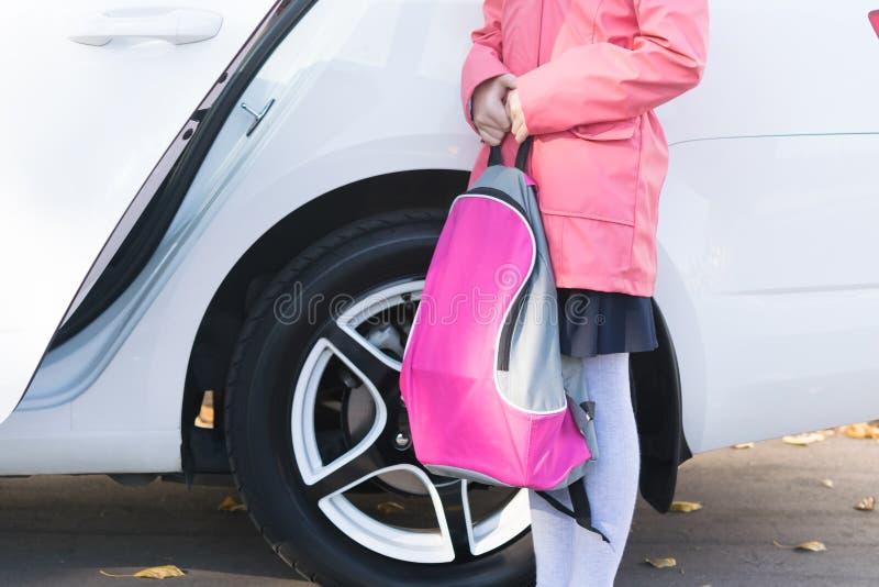 Por la mañana una muchacha se está colocando en el coche con un bolso para los libros de texto antes de ir a enseñar fotos de archivo