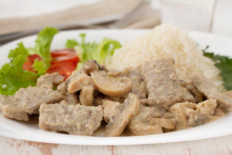 Porc avec des champignons de couche, riz bouilli photos libres de droits