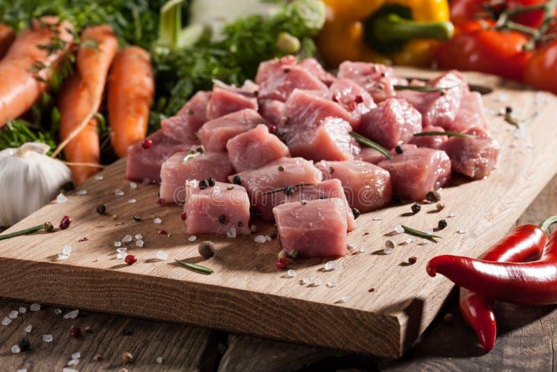 Porc cru sur la planche à découper et les légumes frais photos stock