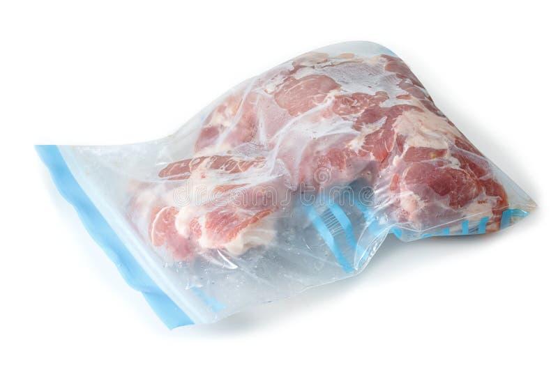 Porc cru surgelé enveloppé dans le sachet en plastique photographie stock libre de droits