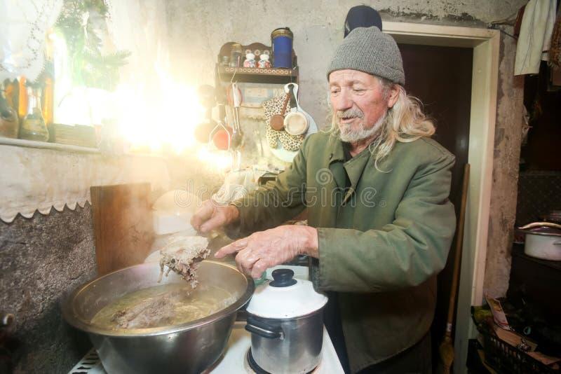 Porc de ébullition de vieil homme images stock