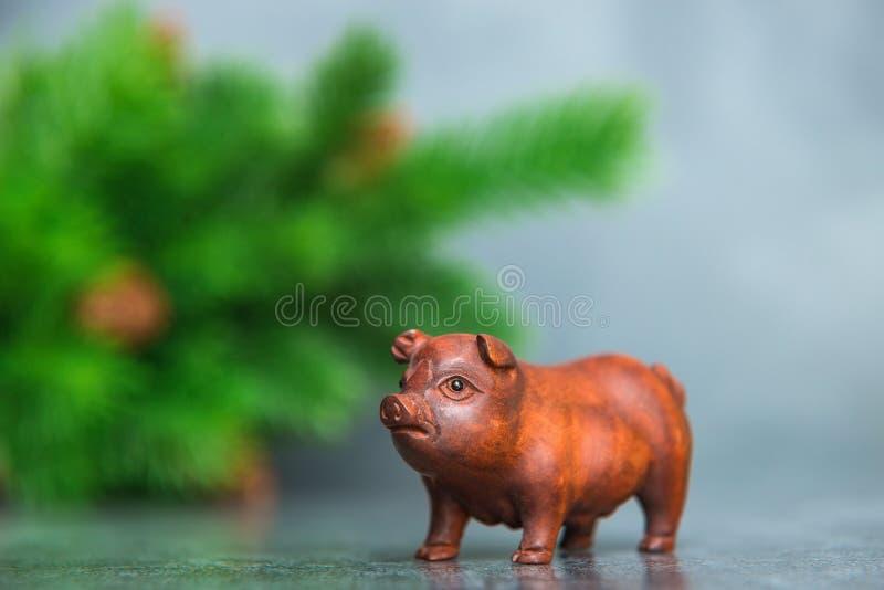 Porc en bois, symbole de nouvelle année, sur le backgroun gris d'arbre de Noël photo libre de droits