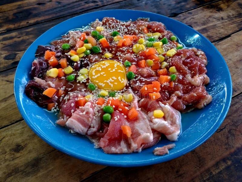 Porc et oeufs crus avec le sésame, le maïs, les carottes et les haricots blancs dans un plat bleu sur une vieille table en bois photo libre de droits