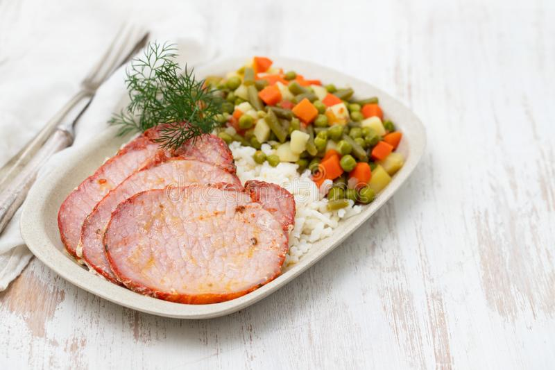 Porc frit avec du riz et les l?gumes bouillis sur le plat photo libre de droits
