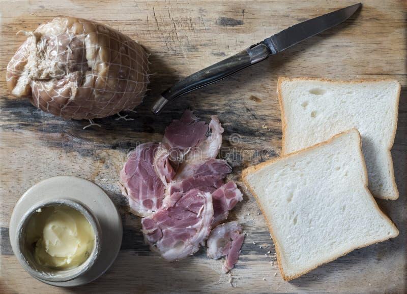 Porc fumé vietnamien, beurre dans le pot, couteau traditionnel français, et pain sur un conseil en bois images stock