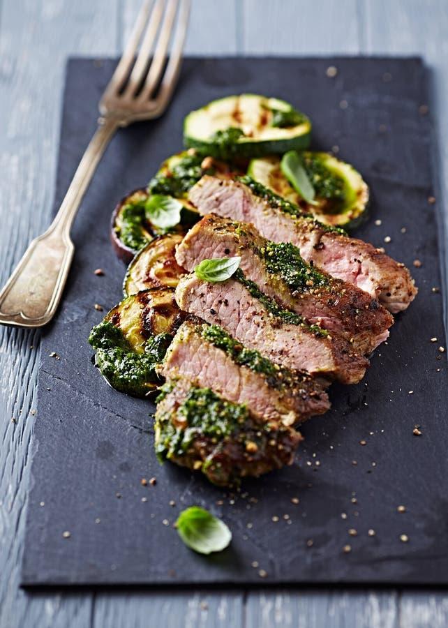Porc grillé avec le Salsa Verde et la courgette, coupée en tranches photo libre de droits