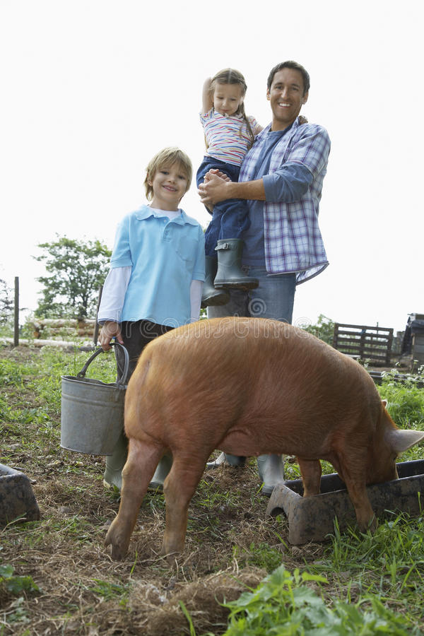Porc heureux d'And Children With de père dans l'étable photographie stock libre de droits