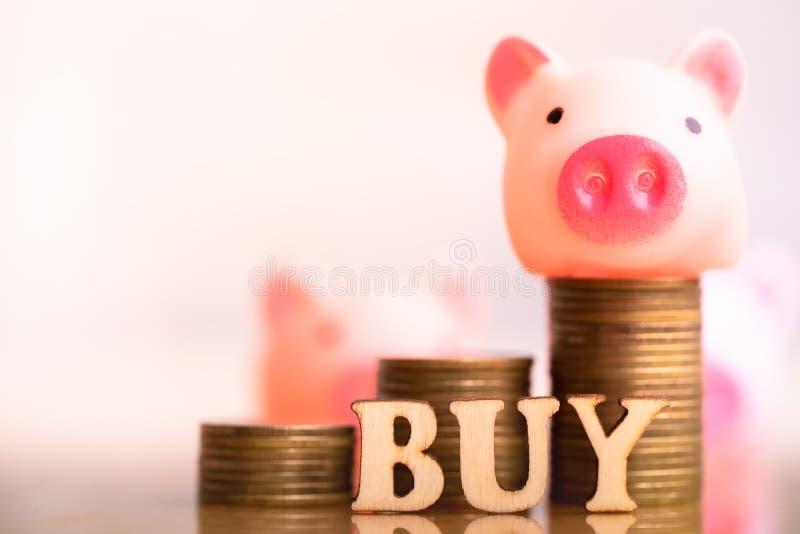 Porc sur le mot ACHAT de pile de pièces de monnaie et de bloc en bois photographie stock