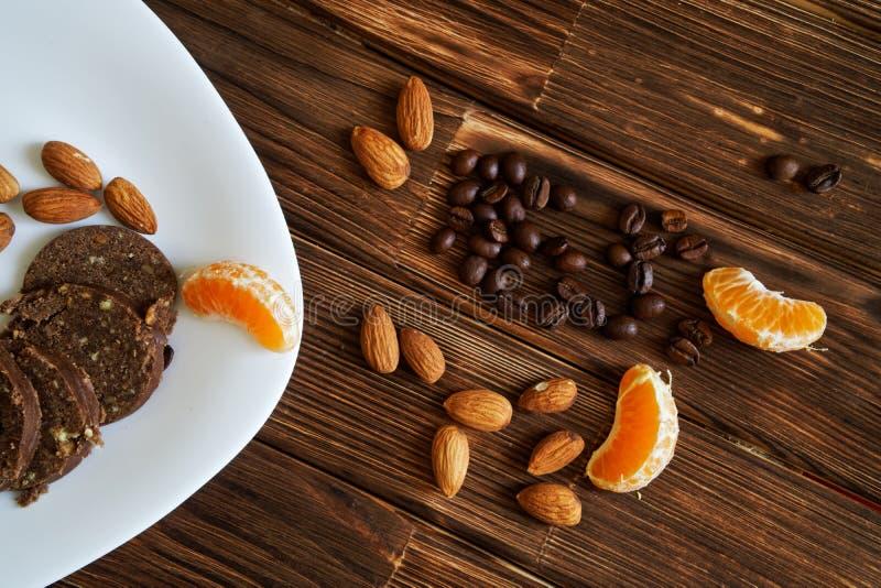 Porcas da amêndoa, grãos de café, fatias da tangerina e pastelaria da salsicha do chocolate em uma superfície de madeira foto de stock