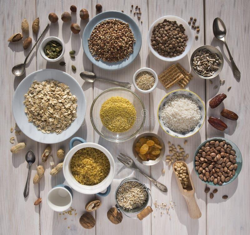 Porcas diferentes, cereais, passas em placas em uma tabela de madeira Cedro, caju, avelã, nozes, amêndoas, sementes de abóbora, g fotografia de stock