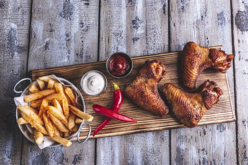 Porcas grelhadas das asas de galinha, das batatas fritas, as brancas e as vermelhas do molho em uma superfície de madeira fotografia de stock royalty free