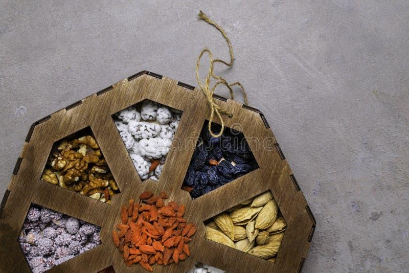 Porcas misturadas em um fundo cinzento na caixa de madeira Alimento e petisco saudáveis Vista superior imagem de stock royalty free