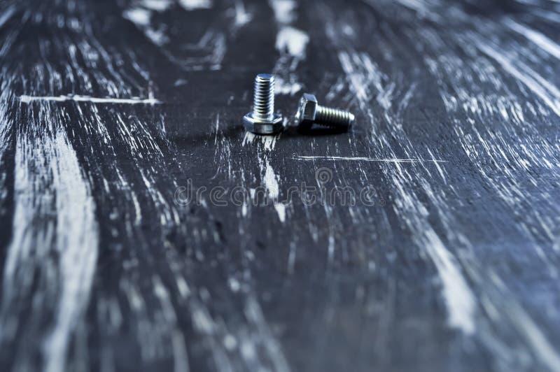 Porcas para os reparos que encontram-se em uma tabela de madeira Porcas do ferro e parafusos f foto de stock royalty free