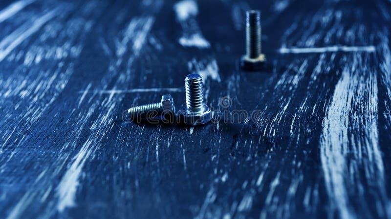 Porcas para os reparos que encontram-se em uma tabela de madeira Porcas do ferro e parafusos f foto de stock