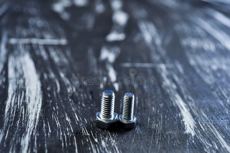 Porcas para os reparos que encontram-se em uma tabela de madeira Porcas do ferro e parafusos f fotografia de stock royalty free
