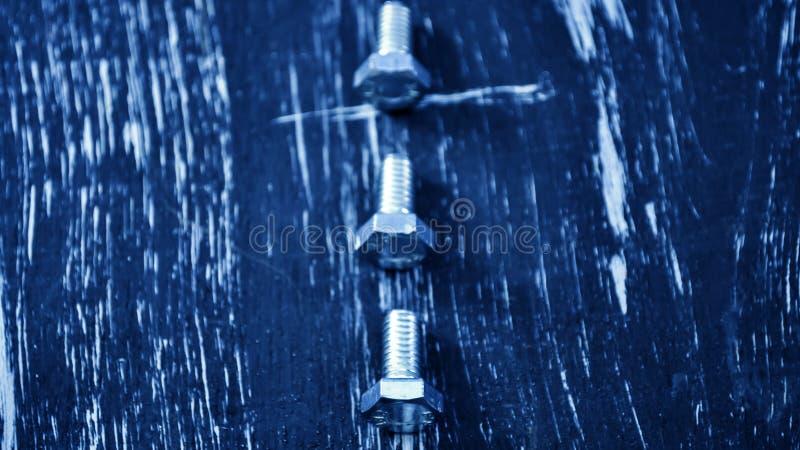 Porcas para os reparos que encontram-se em uma tabela de madeira Porcas do ferro e parafusos f imagens de stock